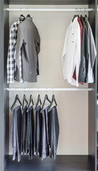 row of pants and shirts in wardrobe