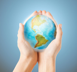 close up of human hands with earth globe