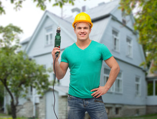 happy male builder in helmet with electric drill