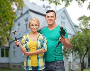smiling couple with hammer and drill over house