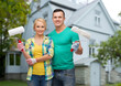 smiling couple with paint rollers over house