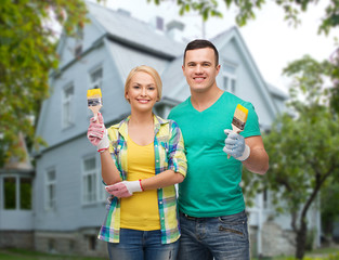 smiling couple with paint brushes over house