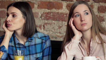 Offended and bored female friends sitting in cafe