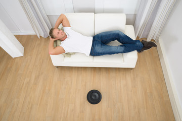 Relaxed Man With Robotic Vacuum Cleaner On Floor