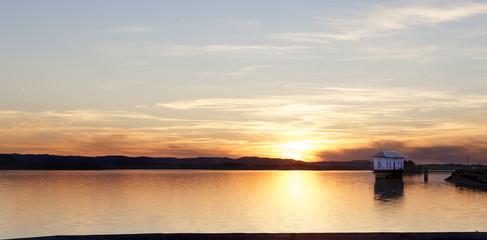 Paisaje puesta del sol. Casa solitaria y lago