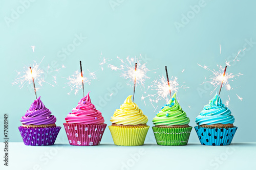 Foto Spatwand Koekjes Colorful cupcakes with sparklers