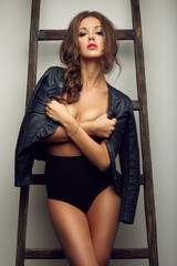 beautiful sexy woman topless in leather jacket near the ladder