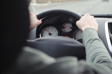 Man driving a car. Hands on steering wheel of a car.