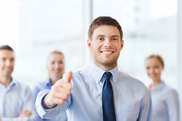 smiling businessman showing thumbs up in office