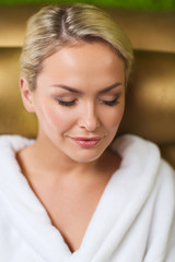 close up of woman sitting in bath robe at spa