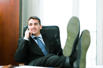 Businessman sitting in a chair and talking on mobile phone