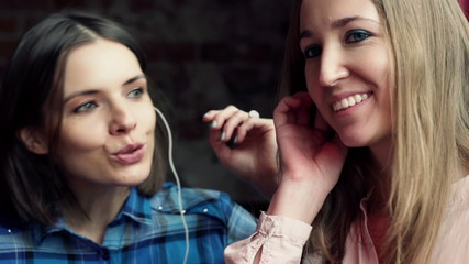 Happy girlfriends listen to music on smartphone in cafe