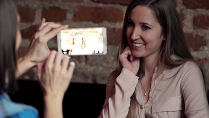 Two happy girlfriends taking photo with smartphone in cafe