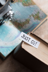 """""""Just go"""" book and map. Travel  concept."""