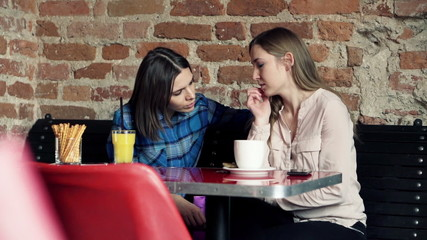 Young woman comforting her sad friend in cafe
