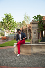 Attractive young man reading a magazine near the fountain.