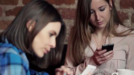 Beautiful girlfriends using smartphone in cafe