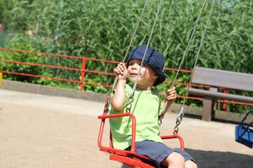 Junge sitzt im Kettenkarussel