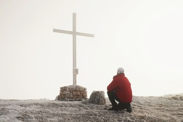 Tourist stand at cross of memorial on mountain peak  in Alps.