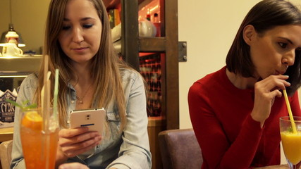 Beautiful girlfriends with smartphone and tablet in cafe
