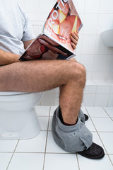 Man In Toilet Holding Sexy Magazine