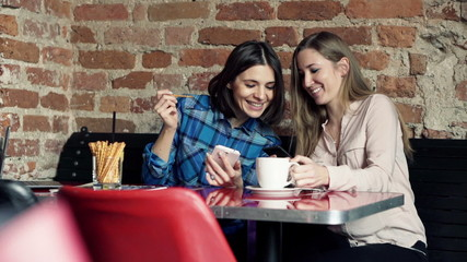 Beautiful girlfriends chatting over smartphone in cafe