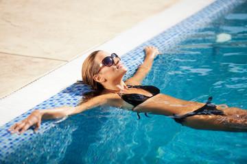 Beautiful woman in bikini relaxing in the swimming pool