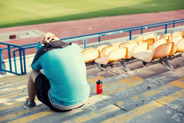 tired sportsman after failing at stadium