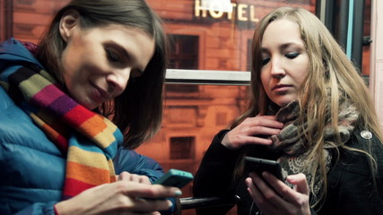 Young happy women with smartphone on tram