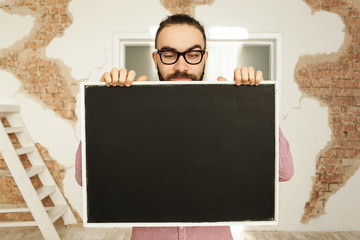 Man in glasses holding blank blackboard in hands