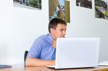 Young man sitting working on a laptop