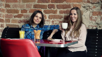 Beautiful happy girlfriends sitting by table in cafe