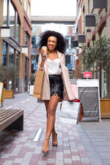 young woman walking with a coffee and shopping bags