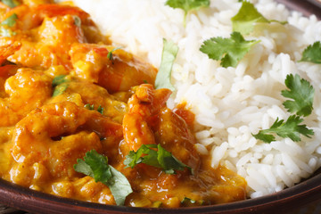 Shrimps in curry sauce with rice and cilantro macro horizontal