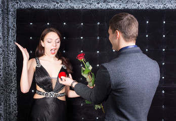 Boyfriend Offering a Ring and Rose to Girlfriend