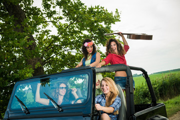 Excited women having fun on a jeep.