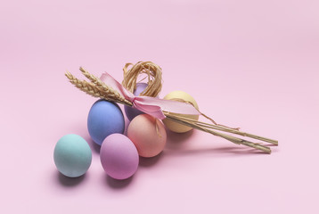 Easter composition of colorful eggs and sheaf of wheat