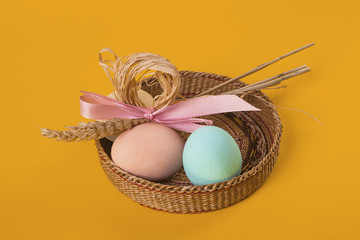 Easter composition of three painted eggs and sheaf of wheat