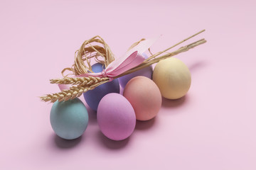 Colorful Easter eggs composition and sheaf of wheat