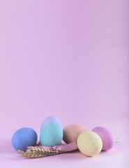 Colorful Easter eggs composition with sheaf of wheat vertical ca