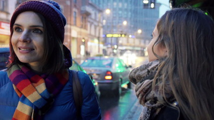 Young happy beautiful girlfriends talking in city