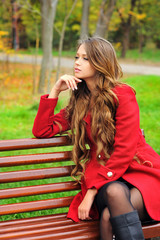 Woman dressed in red coat sitting in autumn park.