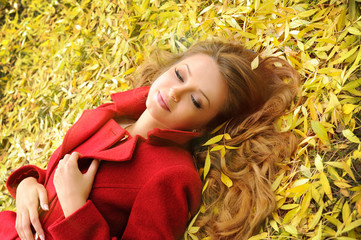 Smiling woman in red coat lying in autumn leaves in park.