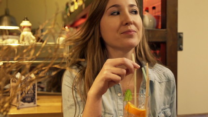 Portrait of beautiful woman drinking cocktail in cafe