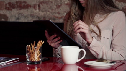 Close up of woman hands with tablet computer in cafe