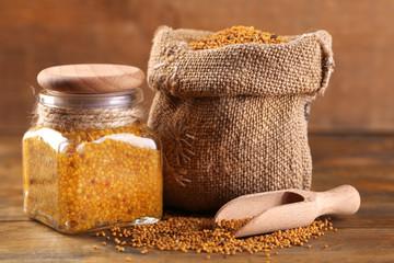 Mustard seeds in bag and Dijon mustard in glass jar