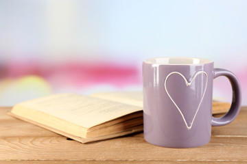 Cup of tea and book on table, on bright background
