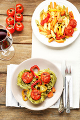 Two kinds of tasty pasta with pepper, carrot and tomatoes