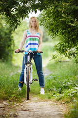 Young blonde woman on a bicycle in the forest