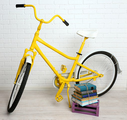 Bicycle with books on brick wall background